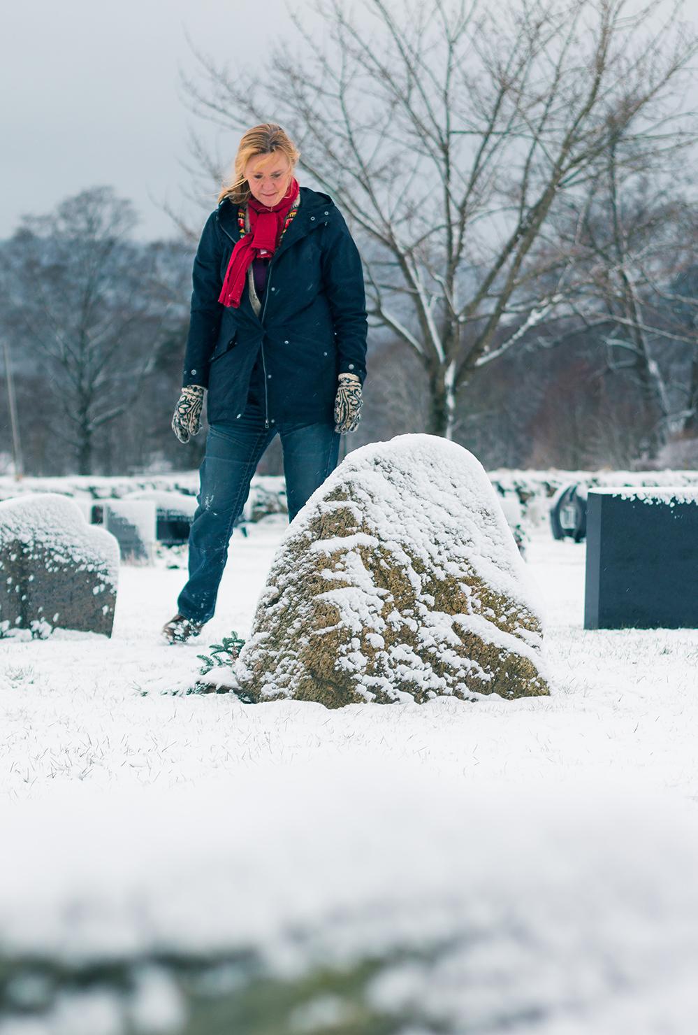 Mette Taansberg ser ned på sin ektemanns gravstein paa kirkegaarden