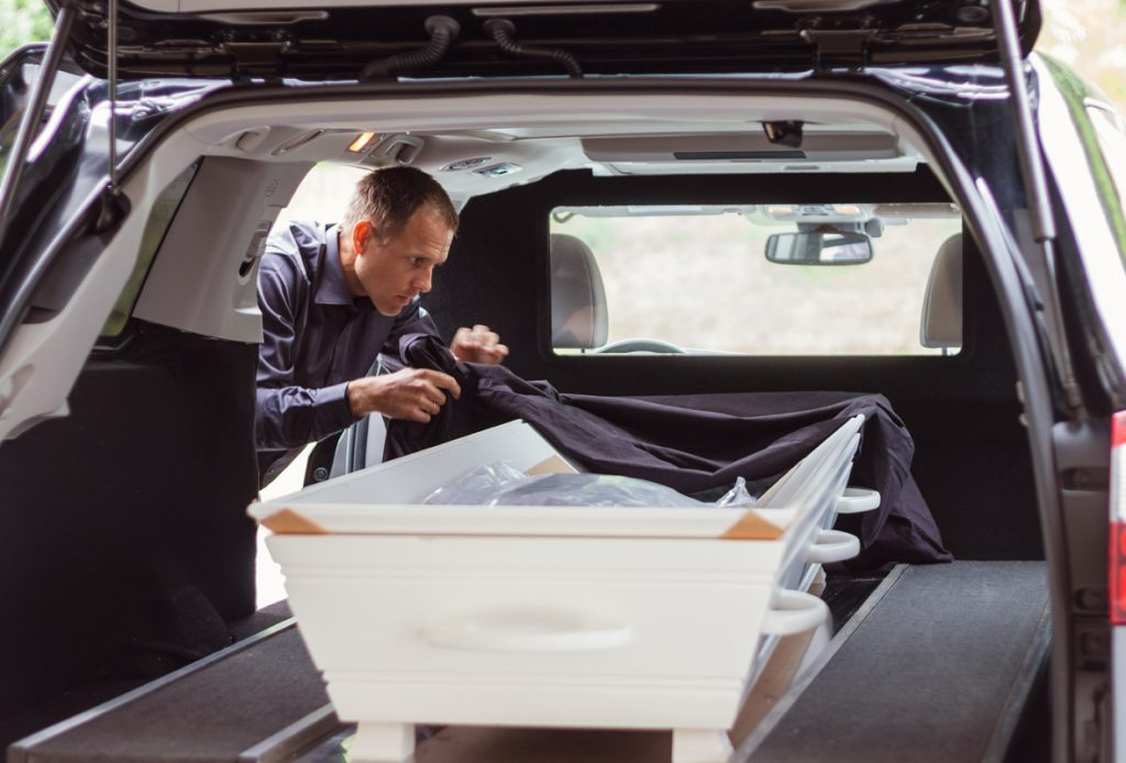 Martin Lande legger duk på kiste i begravelsesbil